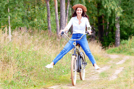 Woman riding on a bicycle in a summer park or forest Foto de archivo