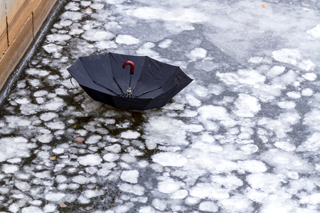 abandoned umbrella on an ice of city river or lake 免版税图像