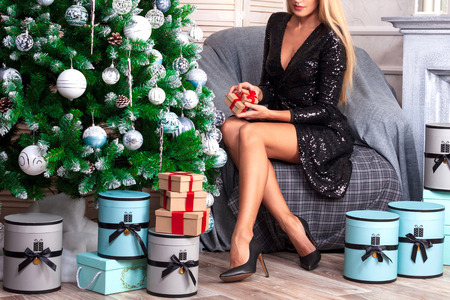 Woman with beautiful long tanned legs wearing black dress sitting in an armchair near by the christmas tree