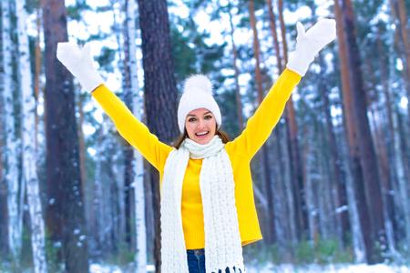 Jolie jeune femme souriante dans une forêt ou un parc d'hiver