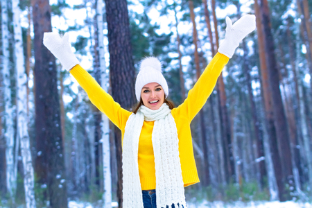 Pretty young smiling woman in a winter forest or park