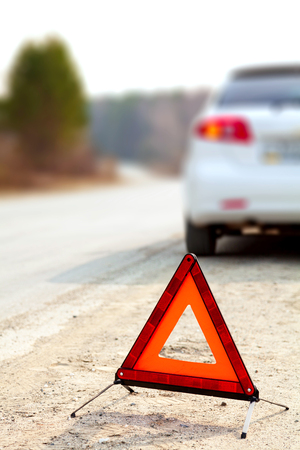 White car and a red triangle warning sign on the road Reklamní fotografie