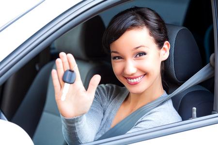 Junge glückliche Fahrerin hält Autoschlüssel in ihrem neuen Auto