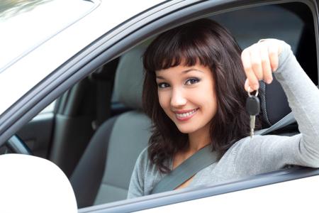 若い幸せな女性のドライバーは彼女の新しい車で車のキーを保持します