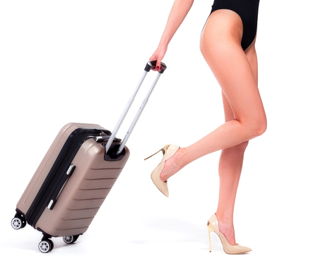 Closeup shot of woman who is pulling a suitcase, isolated on a white background, summer vacations concept Standard-Bild