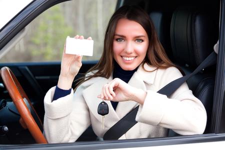 Glückliches Mädchen in einem Auto, das einen Schlüssel und eine leere weiße Karte für Ihren Text zeigt