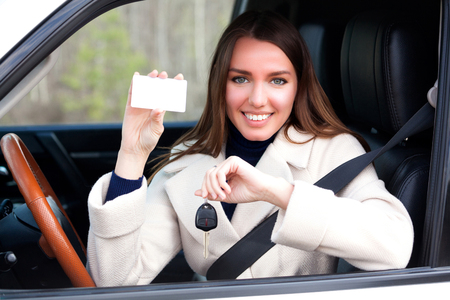 Happy girl in a car showing a key and an empty white card for your text