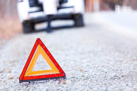 Closeup shot of warning red triangle sign, broken car and girl