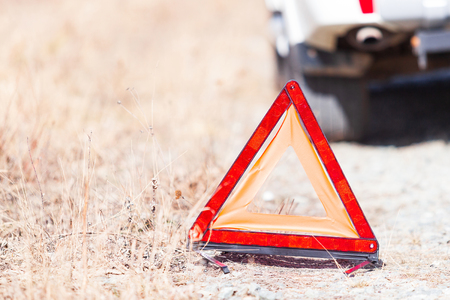 Closeup shot of the red emergency stop sign and broken white car on the roadside Reklamní fotografie
