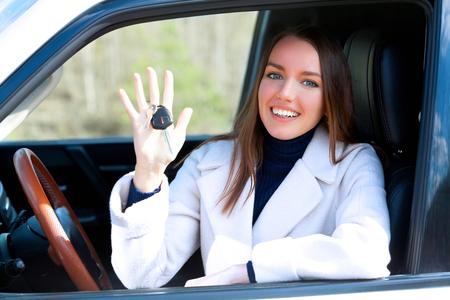 Conductor de mujer feliz con llaves de coche sentado en coche blanco con ventana abierta