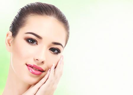 Close-up shot van mooie vrouw met schone, frisse huid, abstracte groene onscherpe achtergrond met copyspace Stockfoto