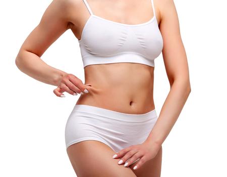 La femme pince la graisse sur son ventre, tir de plan rapproché