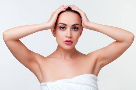 Schönheitsporträt der jungen Frau im weißen Tuch nach der Dusche. weißer Hintergrund