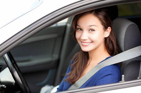 Feliz dueño de un auto nuevo. Conductor de mujer bonita sonriéndole desde su automóvil