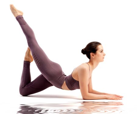 Beautiful young woman doing yoga or pilates exercise, isolated on white background.  Healthy life concept