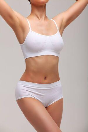 Mujer delgada delgada en ropa interior blanca posando sobre fondo blanco. Concepto de bienestar y cuidado corporal. Estilo de vida saludable