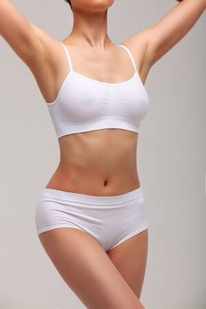 Slim slender woman in white underwear posing against white background. Wellness and body care concept. Healthy lifestyle