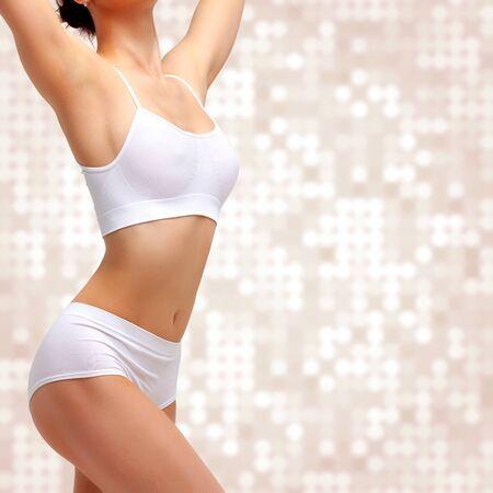 Donna snella esile in biancheria intima bianca in posa su sfondo astratto. Concetto di benessere e cura del corpo. Uno stile di vita sano