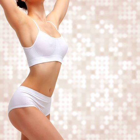Mujer delgada delgada en ropa interior blanca posando sobre fondo abstracto. Concepto de bienestar y cuidado corporal. Estilo de vida saludable
