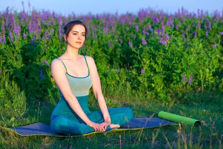 Young woman doing yoga exercise outdoors. Wellness concept