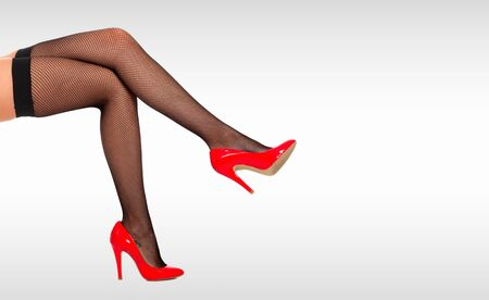 Beautiful female legs in black tights and red shiny shoes against a grey background with copyspace