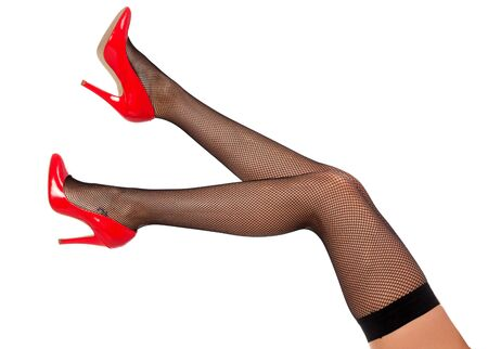 Beautiful female legs in black tights and red shiny shoes, isolated on white background