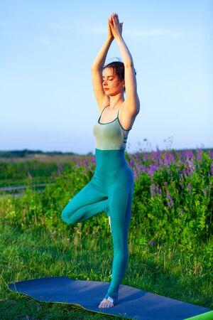 Sportswoman doing yoga excercise in green field