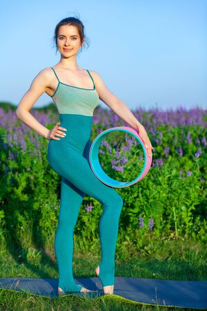 Sporty woman holds a gymnastic wheel, evening light