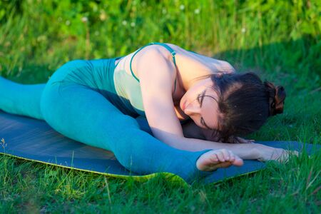 Beautiful young woman doing stretching exercise on green grass in a field or a park.