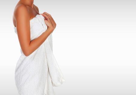 Beautiful young woman with soft white bath towel on her body against a grey background with copyspace Фото со стока - 133669453