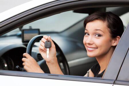 자동차 키를 손에 든 아름다운 소녀 운전사, 새 자동차의 행복한 소유자