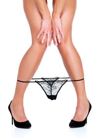 Black panties on slim smooth female legs isolated on white background