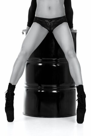Sexy woman with long legs with black strips sitting on a black metal barrel, isolated on white background