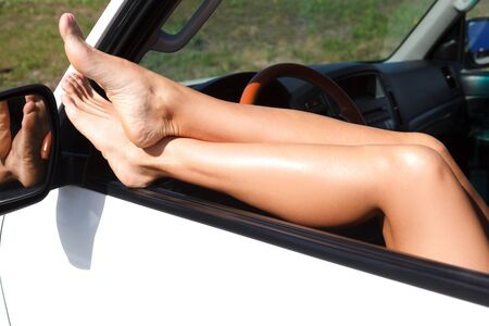 Sexy female legs out of the window of white car