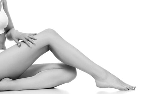 Wellness and beauty concept, beautiful slim woman in white underwear sitting on white floor. Banque d'images