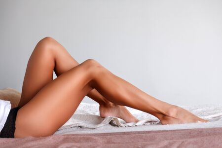 Tanned female legs on a bed Banque d'images - 149587042