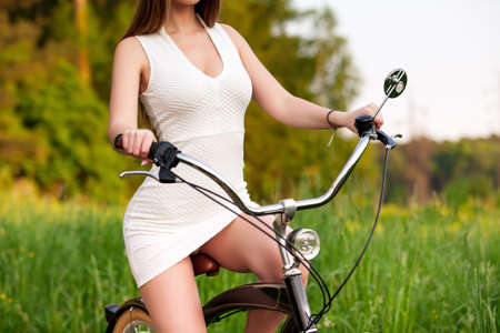 Sexy woman in white dress riding on a black bicycle Imagens