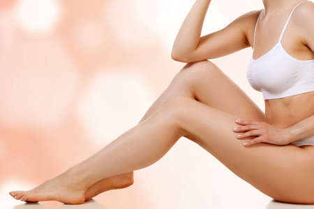 Wellness and beauty concept, beautiful slim woman in white underwear sitting on a floor and smiling to you Banque d'images