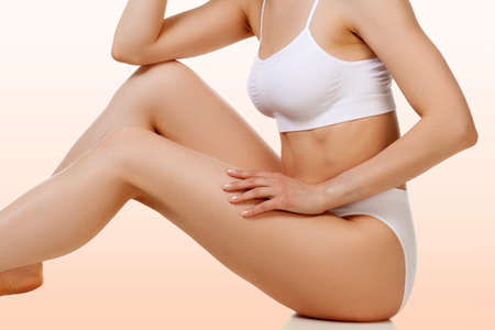 Wellness and beauty concept, beautiful slim woman in white underwear sitting on a floor