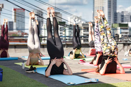 group of young women exercising on the roof by doing yoga Stock Photo