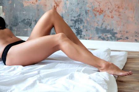 Long woman legs on white sheets