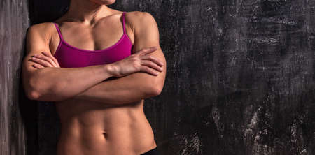Strong muscular woman is posing against grunge wall