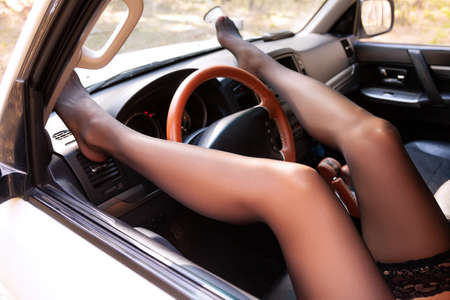 Gorgeous female legs on a dashboard of a car