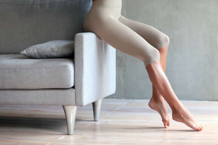 Woman with long slim legs sitting on the edge of the sofa