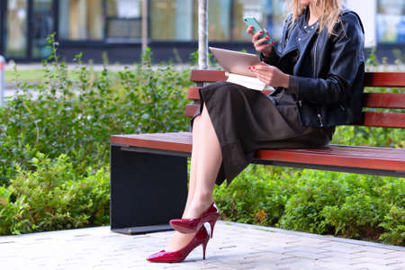 Young woman working with tablet pc and smartphone sitting on a bench in a park Banque d'images