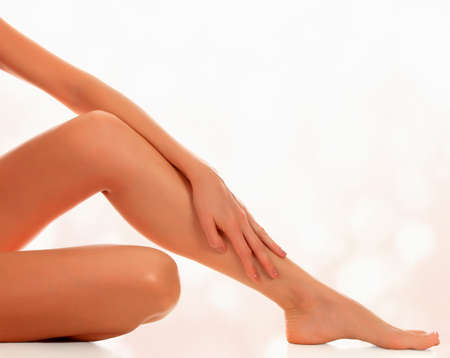 Smooth female legs after depilation, abstract blurred background