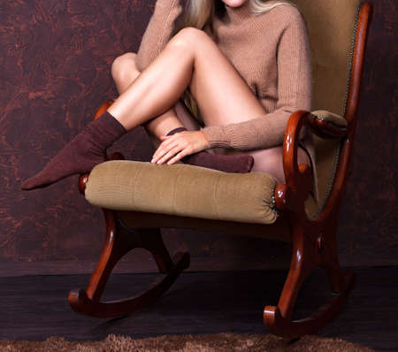 Sexy woman with long slim legs sitting in a rocking chair
