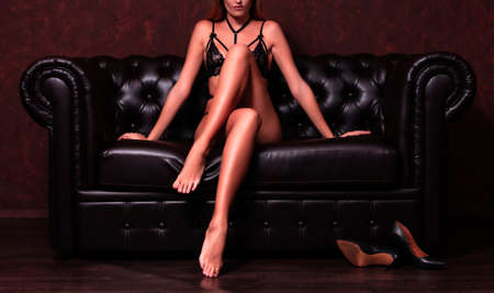 Sexy woman with long slim legs sitting on a leather sofa