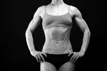 Muscular female torso on black background