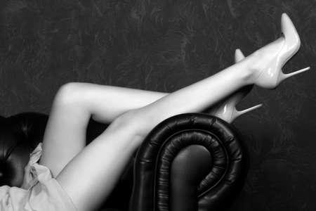 Long legged woman in blue dress lies on a leather sofa